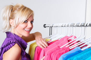 Young woman browsing rack of coloured clothes